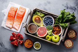 Healthy food clean eating selection in wooden box: fish, fruit, vegetable, seeds, superfood, cereals, leaf vegetable on gray concrete background