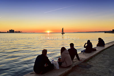 Admiring the sunset on the Tagus river in a quiet evening. Belém, Lisbon. Portugal