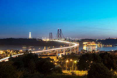 25 de April bridge (similar to the Golden Gate bridge) across the Tagus river and Cristo Rei (Christ the King) on the south bank of the river, in the evening. Lisbon, Portugal