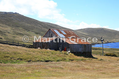 Old wooden farm building with a corrugated iron roof, plus electricity-generating wind turbine, Carcass Settlement, Carcass Island, Falkland Islands