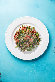 Salad with quinoa, tomato and arugula on white plate on blue background