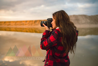 Young woman taking picture on the beach with camera at sunset