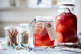 Poached Quince Fruit in a preserving mason jar.