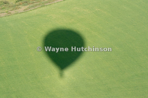 shadow of hot air balloon on countryside, Cumbria, UK.