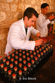 Filling and stamping bottles of olive oil.