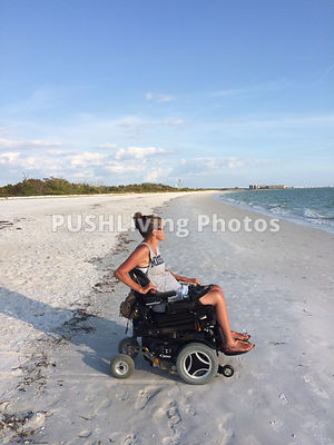 Young woman using a power wheelchair on an ocean beach