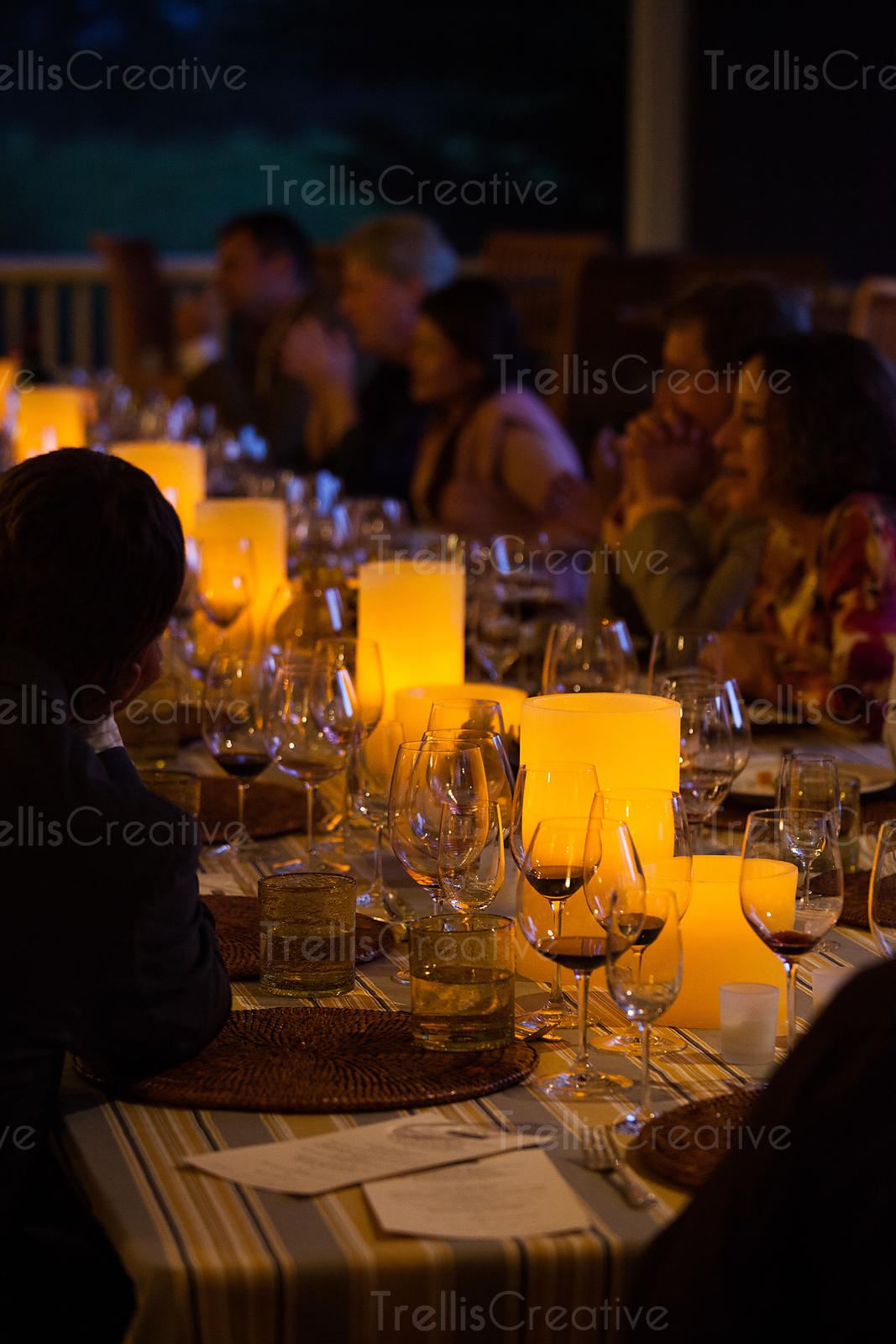 Elegantly decorated candlelit table with people drinking wine