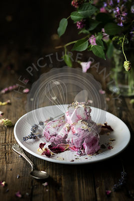 Blueberry ice cream with lavender and rose petals over wooden table