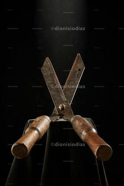 Old gardening scissors on black background