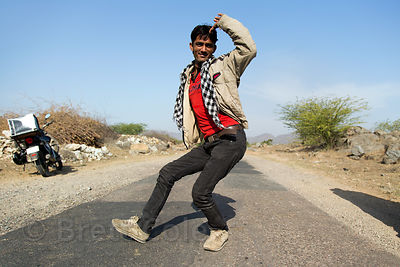A farmer strikes a funny pose on a remote desert road, Chainpura village, Rajasthan, India