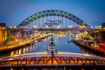 The Swing Bridge and the Tyne Bridge in evening light with reflections of the green illuminated Millenium bridge in the distance.