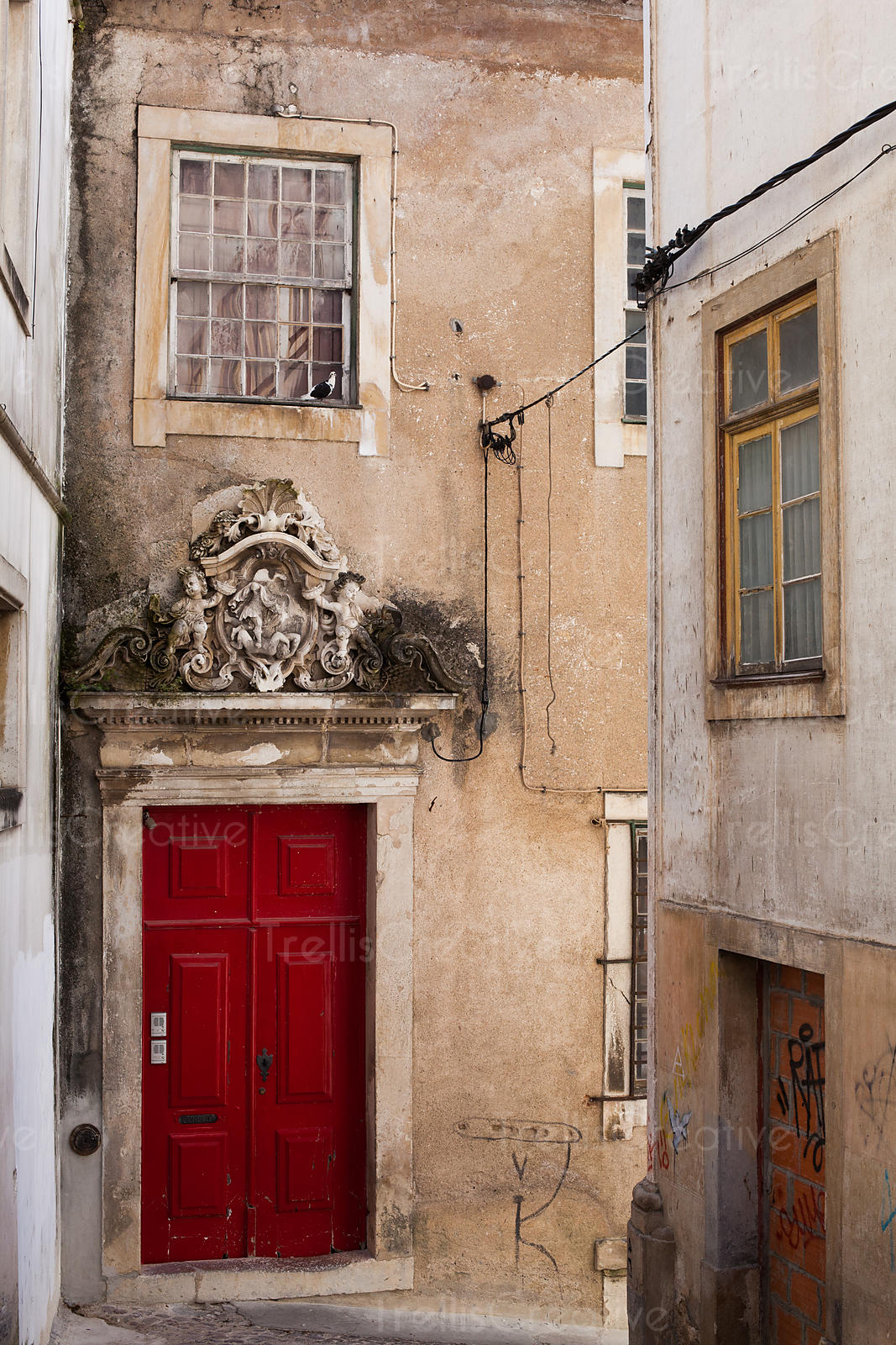 A bright red door pops in an old Portuguese alley way.
