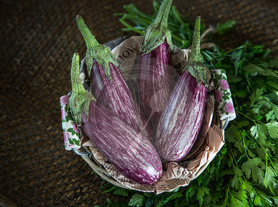Striped aubergines in basket on woven tray
