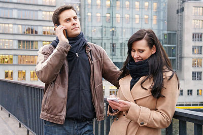 Couple outdoors talking on their cellphones