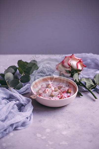 Bowl of yogurt with raspberry powder and dried rose buds
