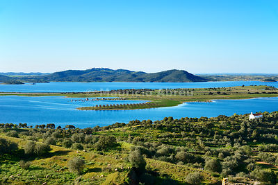 Alqueva dam, the largest artificial lake in Western Europe. On the horizon the hilltop village of Monsaraz. Alentejo, Portugal