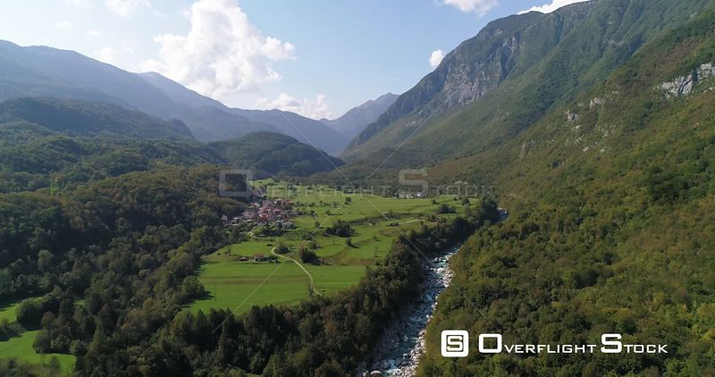 Mountain rapids, C4K aerial drone view over a turquoise soca river, towards a small town, in the alpine nature, near Trigolov national park, on a sunny summer day, in the Julian alps, Slovenia