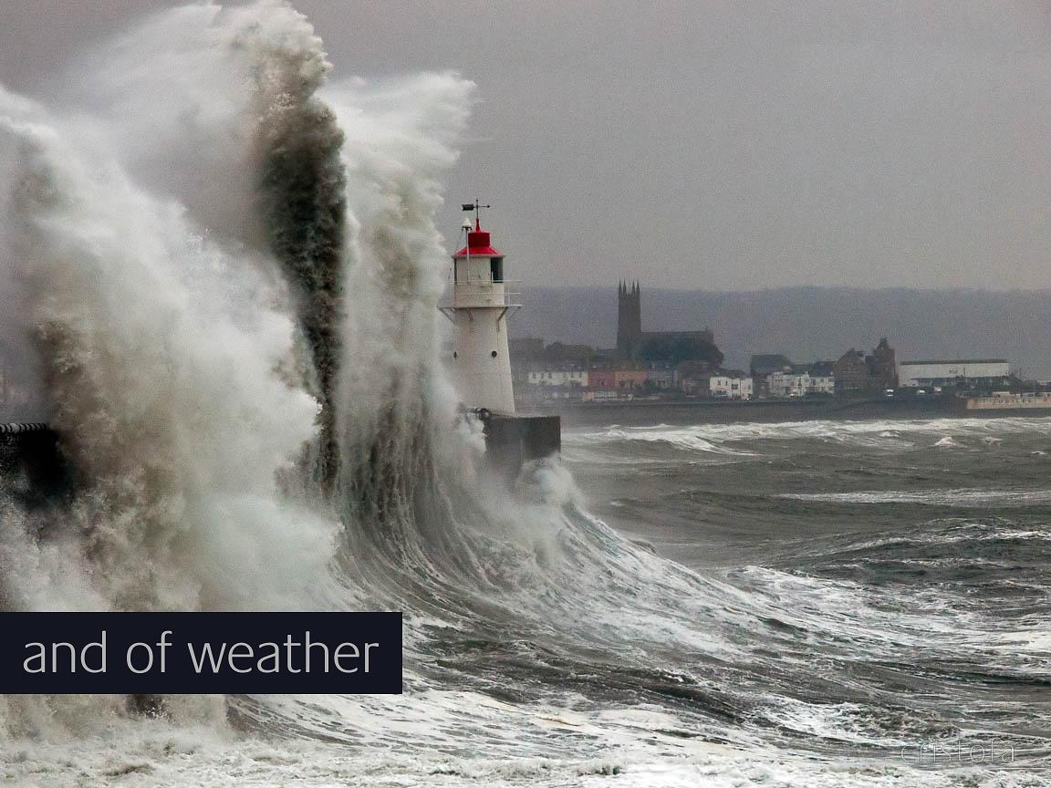 a big wave crashes on the lighthouse pier in Newlyn
