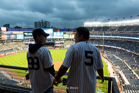 Yankees fans on a stormy night at Yankee Stadium in The Bronx, New York City.