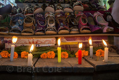 Candles and marigolds adorn a shoe shop during the Diwali festival, Sonapura, Varanasi, India