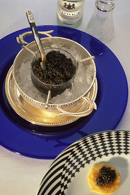A bowl of Ieranian beluga caviar served in the traditional manner on blinis (small pancakes) with vodka, at the Caviar House, Piccadilly, London. Caviar is always scooped with a mother-of-pearl or bone spoon, never metal..