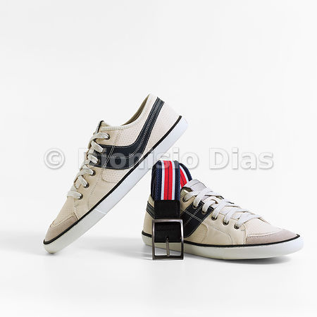 Pair of beige overlapping casual shoe and with woven belt coming out of one of them