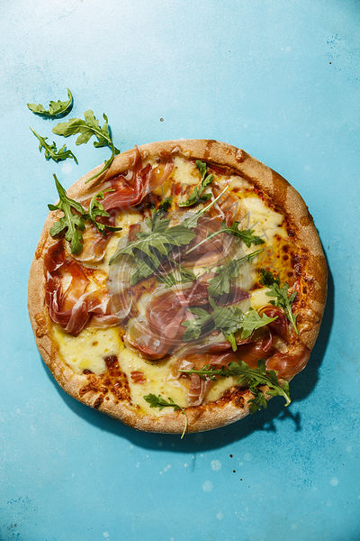 Pizza with mozzarella cheese, prosciutto and arugula leaves on blue background