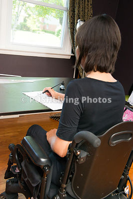 Young female fashion designer using a power wheelchair sketching her new design