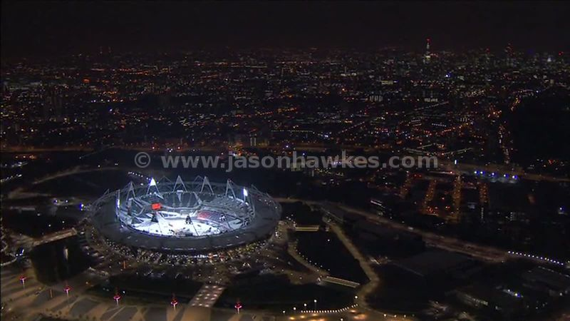 Aerial footage over the Olympic Park and City of London at night, London, England, UK