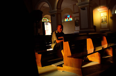 An elderly man prays in a Catholic Church, Tirana, Albania. Religion was banned under the Communist regime