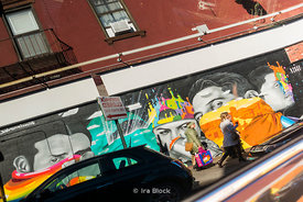 Reflection of mural in a car window on the street in New York City.