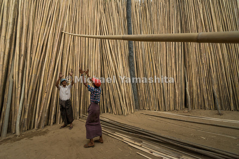 Workers stack poles at an outdoor bamboo market in Myin Kaba, a village outside Bagan. The settlement is known for selling bamboo, a primary building material used to construct everything from homes to rafts to football goalposts.