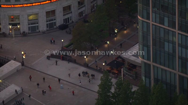 Aerial footage of people walking through Six Public Clocks, Canary Wharf, London