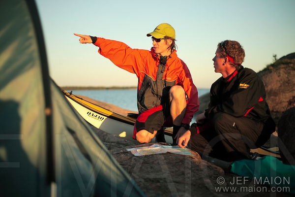 Kayakers styding map and pointing with extended arm