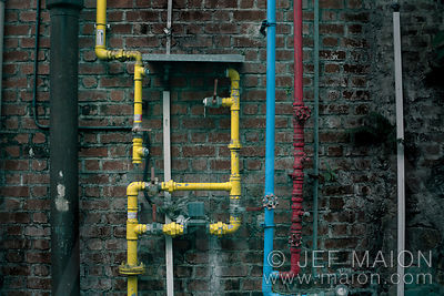 Colorful pipes on brick wall