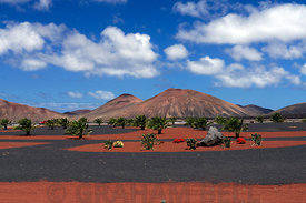 Roundabout on LZ72 road, Yaiza with the volcanoes of Timanfaya National Park in the distance, Lanzarote, Spain.