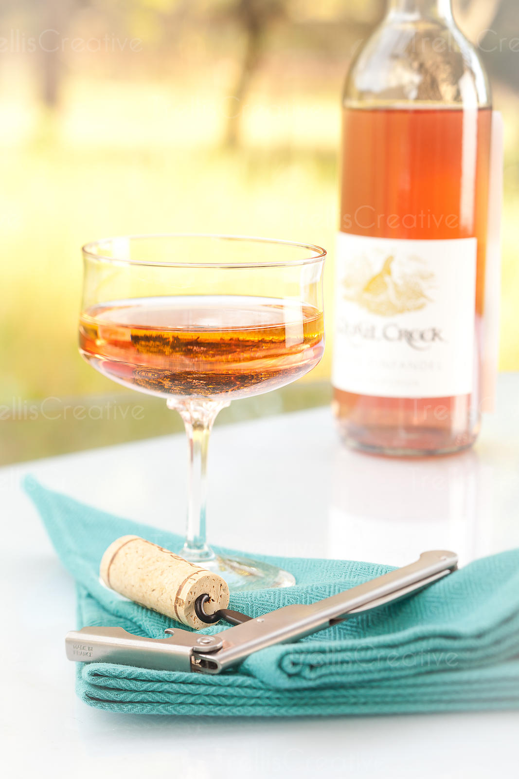 An interesting shaped wine glass with an openend bottle of rose wine on an outdoor patio table