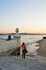 Taking a photograph in front of the Tagus river. Cais das Colunas. Lisbon, Portugal