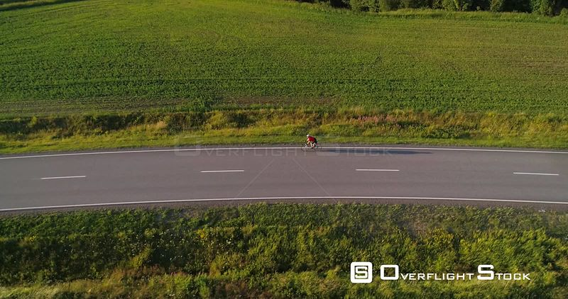 Man biking on the countryside, C4K aerial rising tilt out view following a biker driving on a road, between wheat fields, on a sunny summer evening sunset, in Uusimaa, Finland