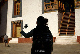 "A woman doing selfie with a cell phone and a selfie handheld stick monopod in the Punakha Dzong, also known as Pungtang Dechen Photrang Dzong (meaning ""the palace of great happiness or bliss"") in Punakha, Bhutan."
