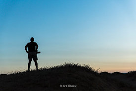 Silhouette of a man with a camera standing on hill in the South Gobi Desert, Mongolia.  In the Khongoryn Els sand dunes in Gobi Gurvansaikhan National Park