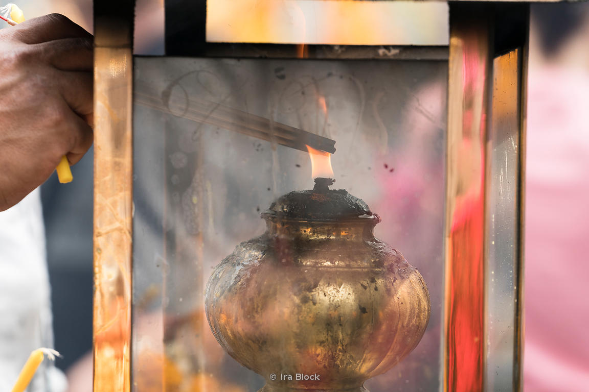 Incense sticks being lit at the Erawan Shrine in Bangkok, Thailand.