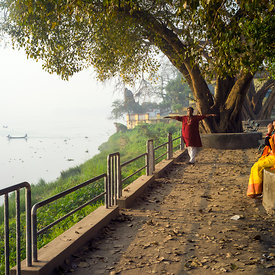 A man and a woman do yogic exercises at dawn on the banks of Hooghley River, Chandannagar