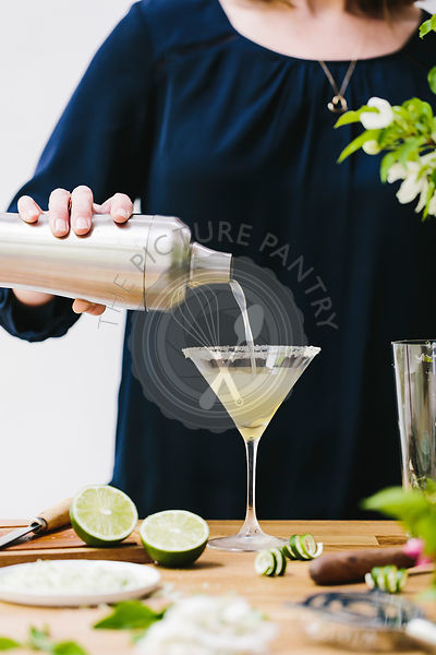 A woman is photographed as she is pouring martini in a glass.