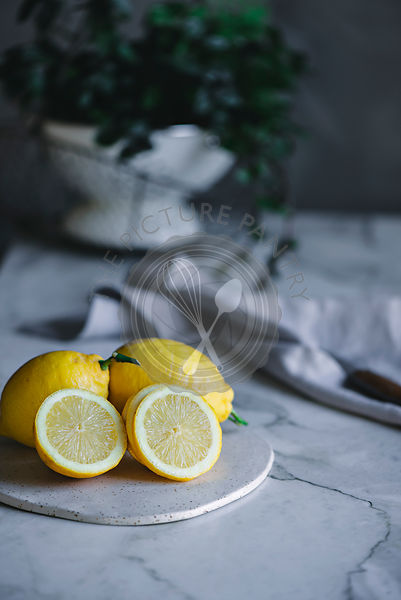 Bright yellow lemons on a marble kitchen surface