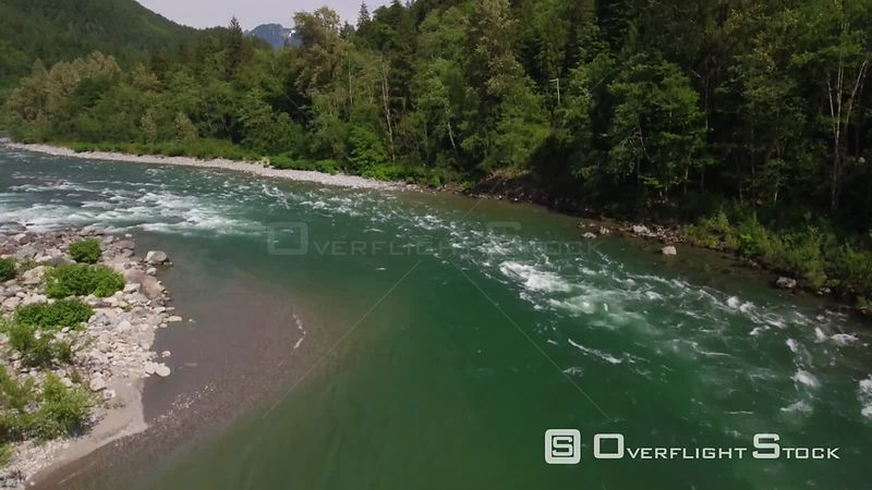 Popup view, starting directly over a rapid river, to reveal towering mountains. Index Washington State
