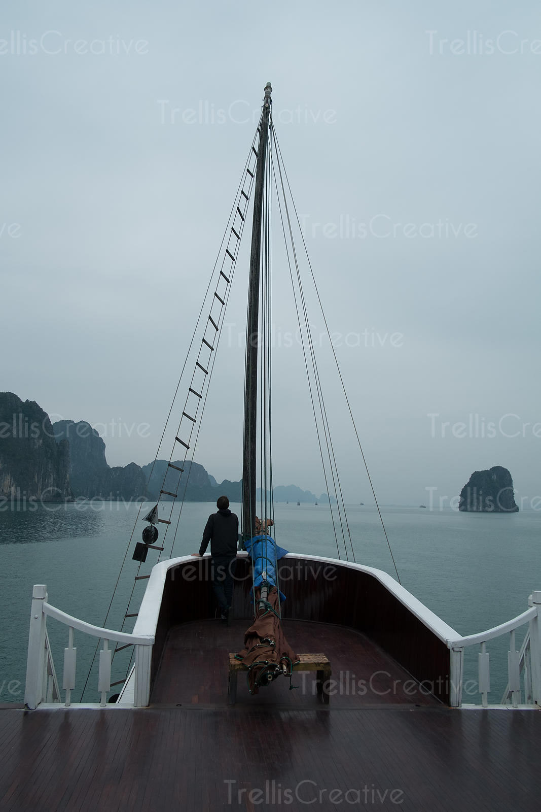 A man standing at the helm of a boat overlooking the view of Halong Bay