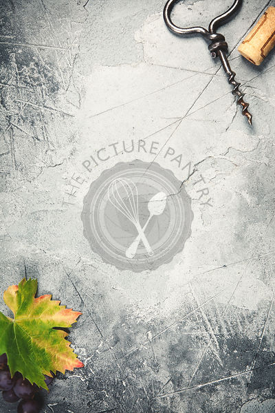 Top view of an old cork screw and grape leaf on gray concrete background with space for text.  A vertical design template for a tasting invitation or restaurant menu