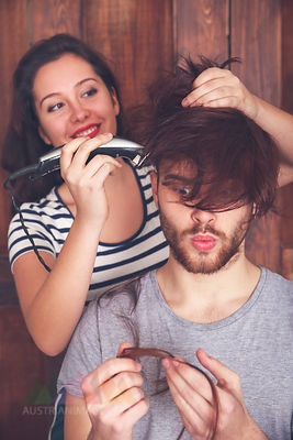 Young man getting a haircut by his girlfriend with hair cutting machine