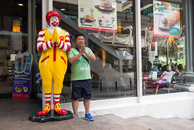 A man taking picture with Ronald McDonalds in Thai style at a shopping mall, Amarin Plaza in Bangkok, Thailand.